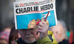A man holds up a copy of Charlie Hebdo at a Bristol vigil