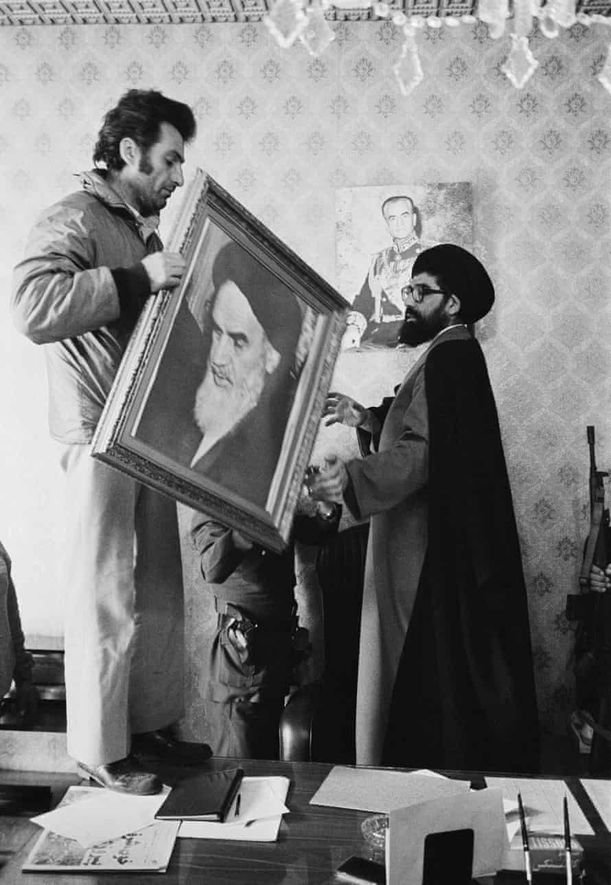 Palace employees replace the portrait of the Shah with Ayatollah Khomeini's at the Niavaran Palace in Tehran on 16 Feb 1979