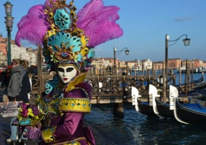 A reveller wearing a traditional volto mask and costume stands beside a group of gondolas