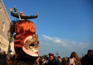 A costumed reveller poses at St Mark's square (Piazza San marco) during the Venice Carnival