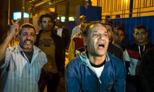 Relatives of Zamalek soccer club fans react and wait outside a morgue in Cairo