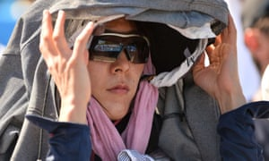 A spectator shields herself from the sun at the 2014 Australian Open tennis tournament in Melbourne.