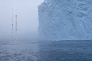 An iceberg inches closer to the remains of a skyscraper