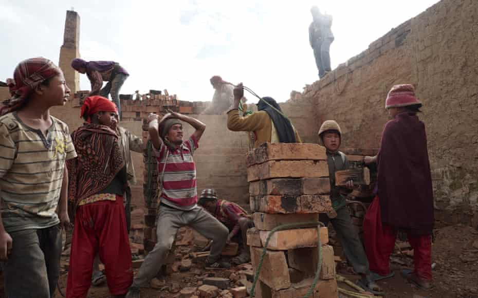Children and adults offload baked bricks from a brick factory in Panchkhal, Dhading district, Nepal. An estimated 28,000 children work in the brick factories in Nepal.