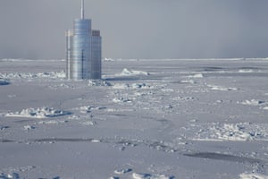 A skyscraper is surrounded by ice