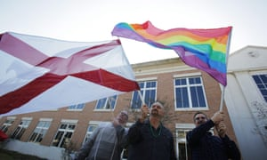 Jason Moreau-McCoy, James Weaver and Darre Foret wave flags in support of same sex marriage outside the county probate court house in Mobile, Alabama.