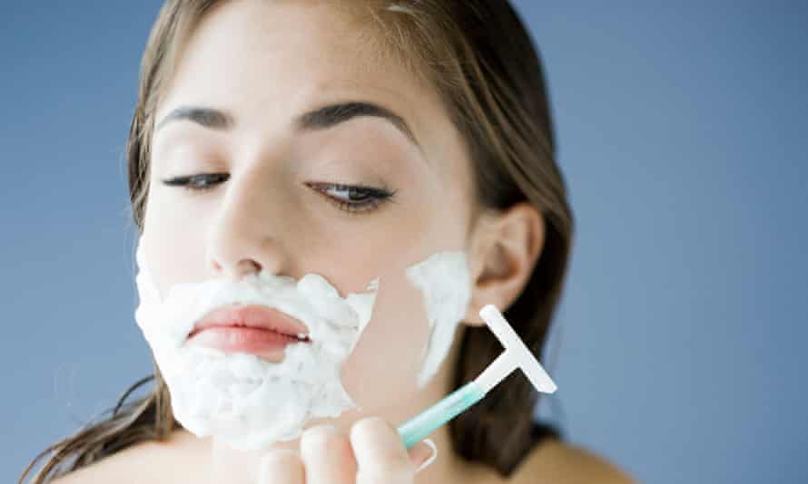 A woman shaving her face with a disposable razor