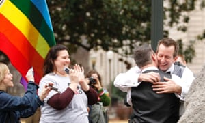 A couple embraces after getting married in a park outside the Jefferson County Courthouse in Birmingham, Alabama.