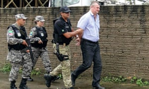 Ezequiel Antônio Castanha (right), who is accused of illegally destroying tens of thousands of square kilometres of Amazon forest, is arrested by federal police officers in Novo Progresso in the northern state of Para, Brazil.