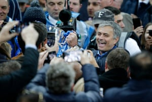 Mourinho shows off the trophy to fans.