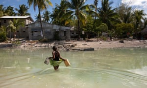 A young girl crosses the lagoon at high tide to get some water for her family, who live on a thin strip of sand that gets cut off from the main island every high tide.r