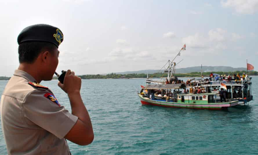 An Indonesian police officer watches a fishing boat carrying asylum seekers.