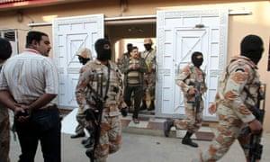 Pakistani paramilitary troops raid the Muttahida Quami Movement's offices in Karachi.
