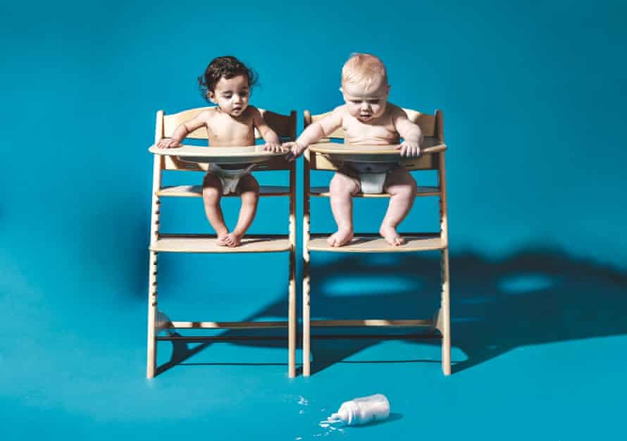 Two model babies in high chairs looking at a dropped bottle of milk on the floor