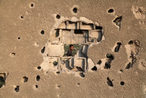 A child looks through a hole in the wall of his home after Israel's attack on Gaza in 2013. Majdi Fathi/NurPhoto/Rex