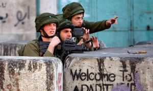 An Israeli soldier photographs clashes with Palestinian stone-throwers in the West Bank city of Hebron on March 6, 2015.