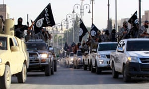 Militant Islamist fighters parade in military vehicles along the streets of northern Raqqa province.