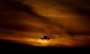 A plane coming in to land at dusk at Heathrow