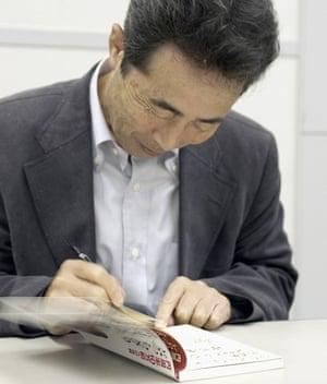 Akira Haraguchi signs his book