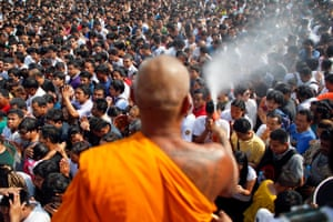A Buddhist monk sprays holy water on the crowd