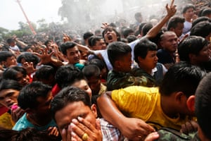 The crowds react as they are sprayed with holy water