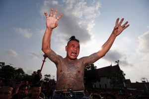 A man a state of trance mimics a creature tattooed on his body