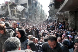 Residents of the besieged Palestinian camp of Yarmouk, queuing to receive food supplies, in Damascus, Syria, in 2014. A new UN-backed report paints a devastated picture of the effect of war on a population.