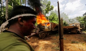 A Ka'apor Indian warrior stands near a burning logging truck in the Alto Turiacu Indian territory, near the Centro do Guilherme municipality in the northeast of Maranhao state in the Amazon basin, August 7, 2014. Tired of what they say is a lack of sufficient government assistance in keeping loggers off their land, the Ka'apor Indians, have sent their warriors out to expel all loggers they find and set up monitoring camps in the areas that are being illegally exploited.
