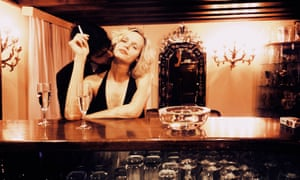 a man kissing a lady's neck while she sits at a bar