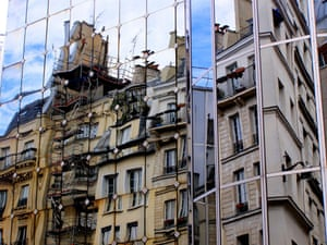 Offices clad in mirrored panels reflect copies of the homes opposite. Walking in Rambuteau, Paris, where each new building, clad in mirrored panels, appears to be a distorted, reverse copy of the old building opposite. This is one of three photos taken one minute apart.