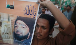 A supporter holds a banner of convicted killer Mumtaz Qadri during a demonstration against his death sentence in Karachi.