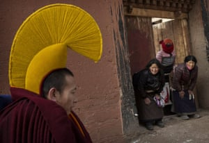 Women bow to a passing monk on his way to take part in special prayers.