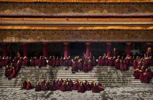 Monks sit on the monastery steps.