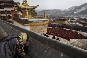 A woman bows her head in prayer as monks take part in special prayers.