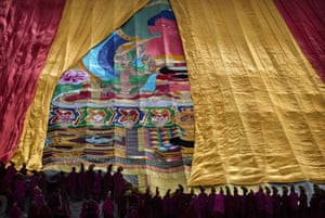 Monks unveil a large thangka, a religious silk embroidery or painting unique to Tibet, showing Buddha.