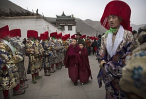 Young monks walk past men in traditional costumes preparing for a procession.