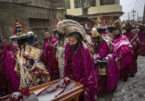 Monks are covered in snow as they take part in a procession.