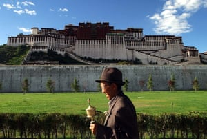 A pilgrim rotates a prayer wheel outside of Potala Palace in Lhasa, Tibet.