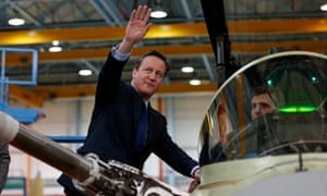 The prime minister, David Cameron, speaking with a worker as he views a military aircraft during his visit to BAE Systems in Preston.
