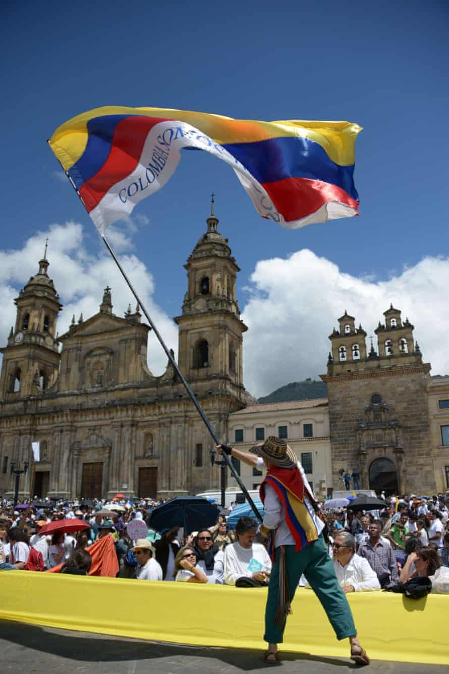 A demonstrator waves a Colombian flag at last week's march in favour of peace talks.