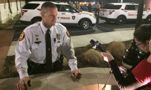 Ferguson officer Lieutenant Gerald Lohr in front of officers guarding the police headquarters.