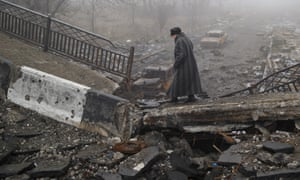 A woman walks across a destroyed bridge, fallen onto the road towards the airport, the scene of heavy fighting in Donetsk.