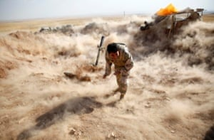 A Kurdish Peshmerga fighter launches mortar shells towards Zummar, controlled by Isis.