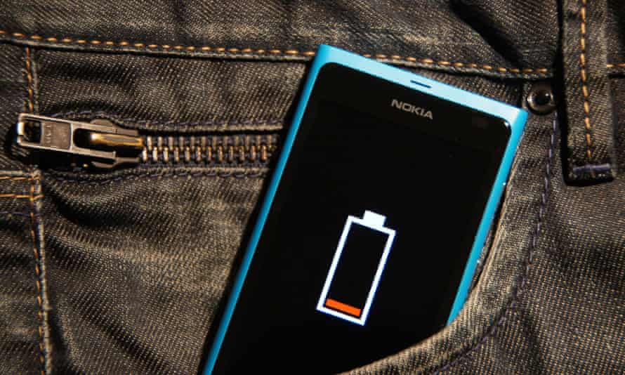 A phone with low battery in a jeans pocket.
