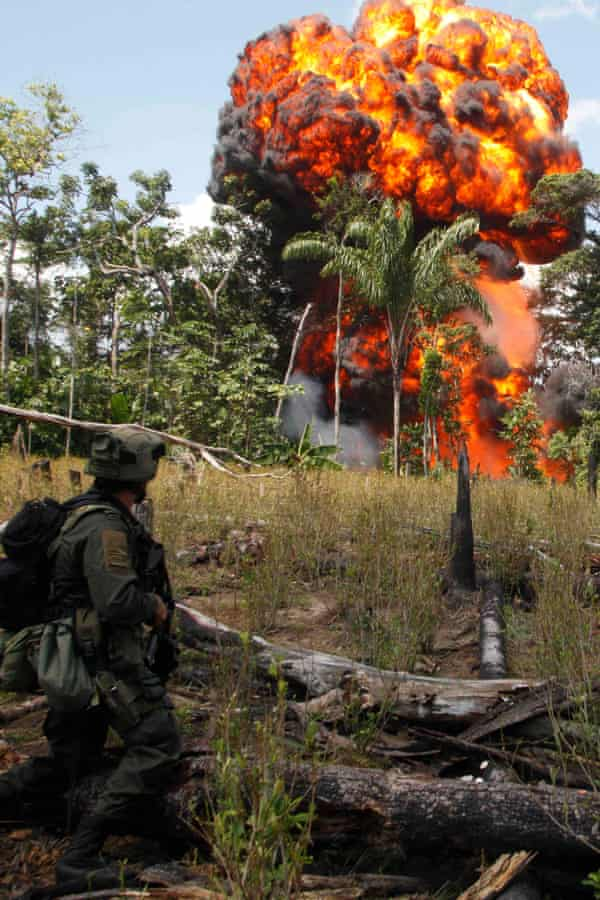 A Colombian anti-drug policeman stands guard after burning a cocaine laboratory in Puerto Concordia near Meta province in 2012.