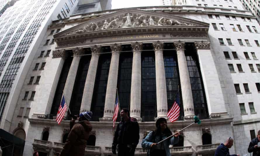 Tourists take pictures with the backdrop of the New York Stock Exchange (NYSE).