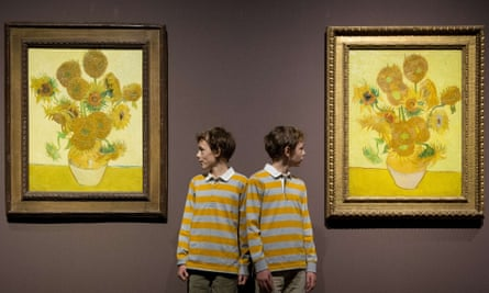 identical twins Edgar and Gabriel pose fwith two version of Van Gogh's Sunflowers at the National Gallery, London, in 2014