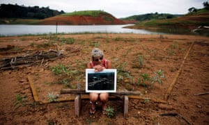 A former resident of the re-emerging old city of the Igarata, Irene De Almeida, 65, holds a photograph of the city before its was submerged in 1969, as she sits on the main street of the old city in front of Jaguari reservoir, in Igarata, Sao Paulo State, February 4, 2015.
