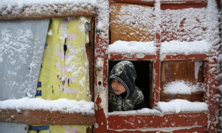 A Syrian boy looks through the door of his snow-covered tent at a refugee camp in the Bekaa valley. Education is at a premium for Syrian refugee children in Lebanon.