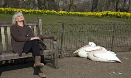 A woman relaxes on a bench next to pelic